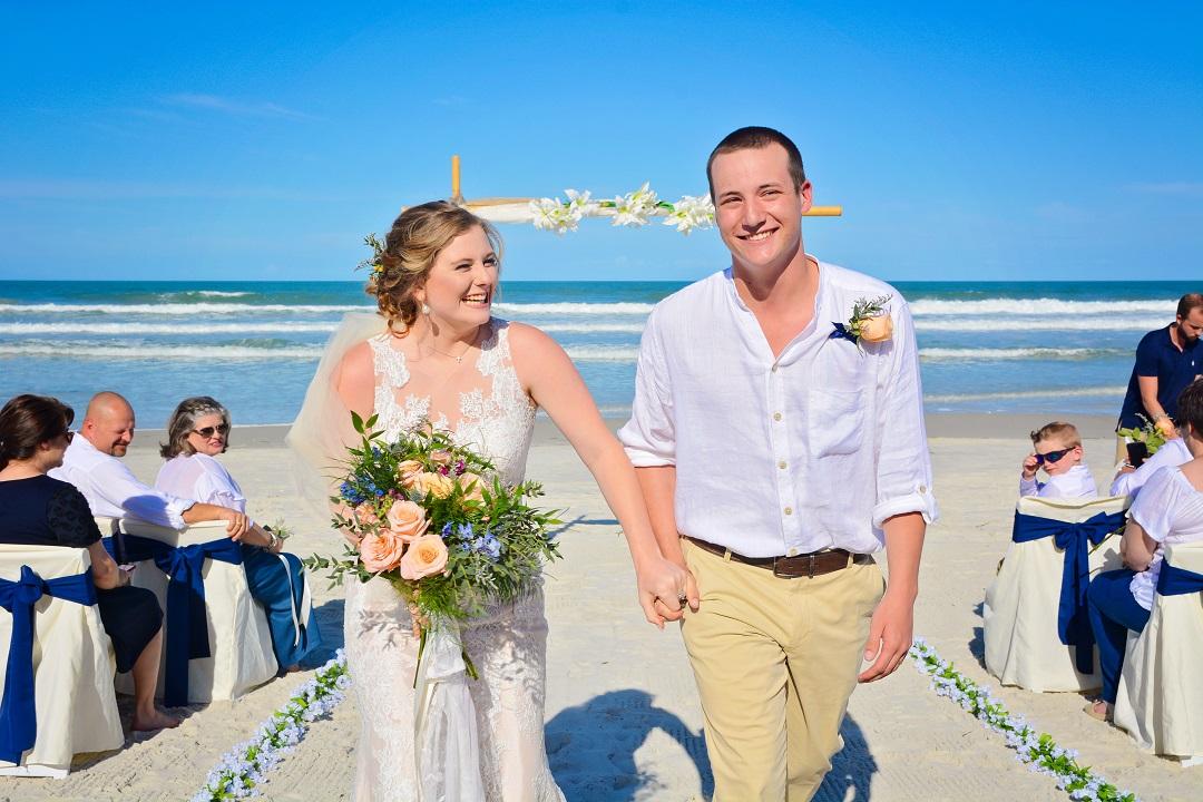 Florida Beach Wedding Bride and Groom holding hands by ocean